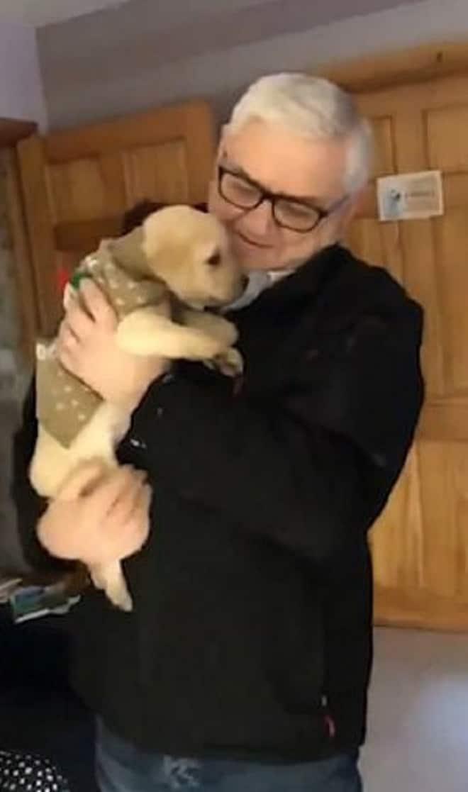 Дедушка держит щенка